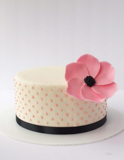 hvid kage med lyserød blomst