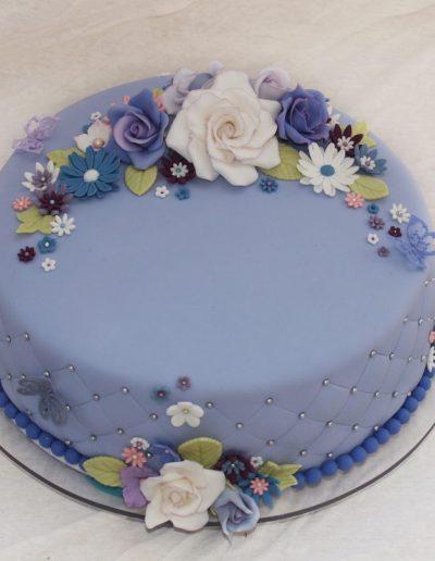 fødeselsdagskage med lilla farver og mange blomster