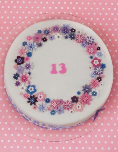 fødselsdagskage med små lyserøde og lilla blomster