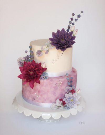 festkage med pink og lilla sukkerblomster