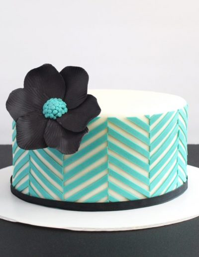 sort og turkis kage med grafisk mønster og stor blomst