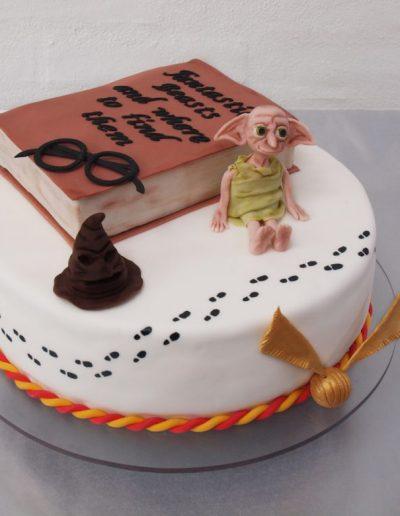 kage til konfirmation med harry potter tema pyntede med fordelingshat, dobby, lynet og bog