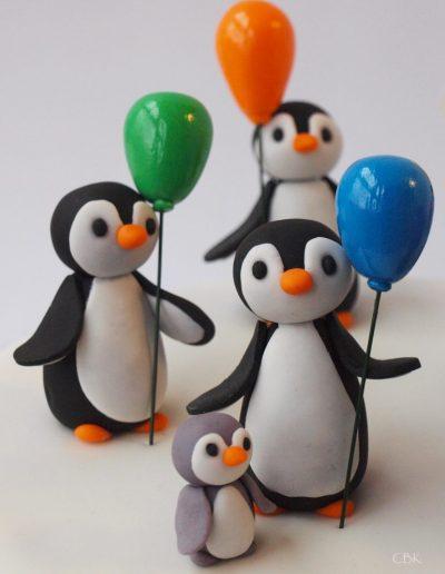 pingviner med balloner pynter på kagen