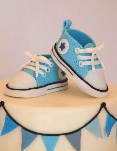 topffigur på dåbskage af små baby converse sko